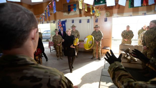 Julie Bishop plays football with Australian troops during her visit on Australia Day.