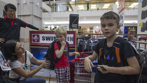 Owen and Toby Street with their mother Jane shopping for new backpacks.