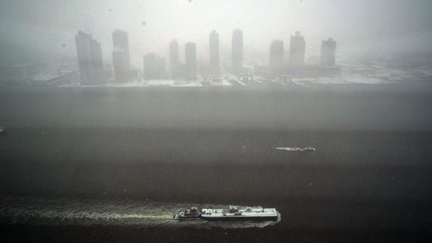 A tugboat sails on the East River during a snow storm in New York on Monday.