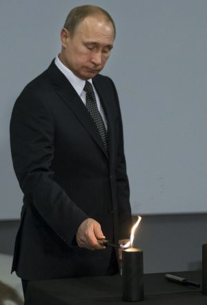 Russian President Vladimir Putin lights a candle.