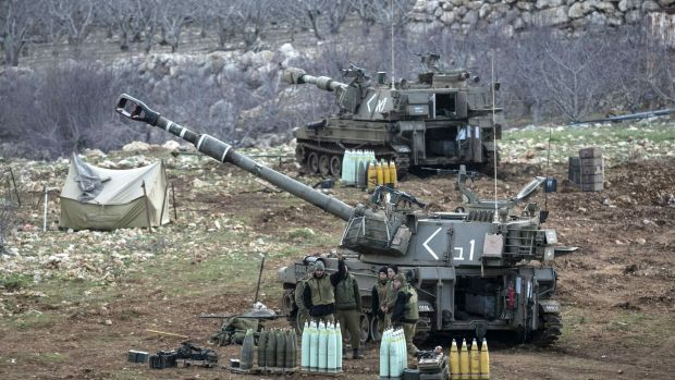 Israeli soldiers stand next to a mobile artillery unit near the border with Syria in the Golan Heights on Wednesday.