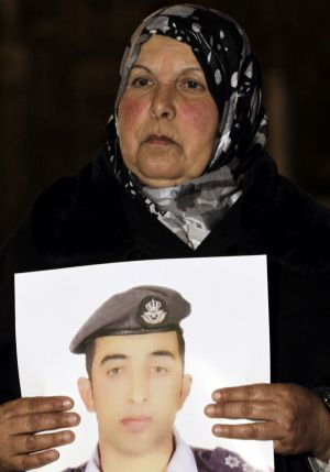 The mother of Jordanian air force pilot Maaz al-Kassasbeh carries a portrait of her son during a protest.