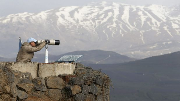 A member of the United Nations Disengagement Observer Force (UNDOF) looks through binoculars at Mount Bental, an ...