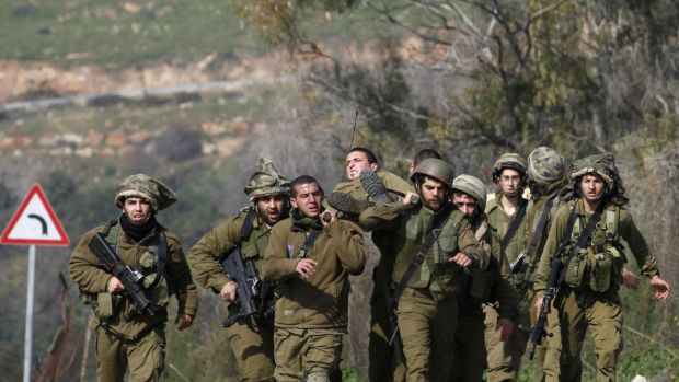 Israeli soldiers carry their injured comrade after an anti-tank missile hit an army vehicle in an occupied area on the ...