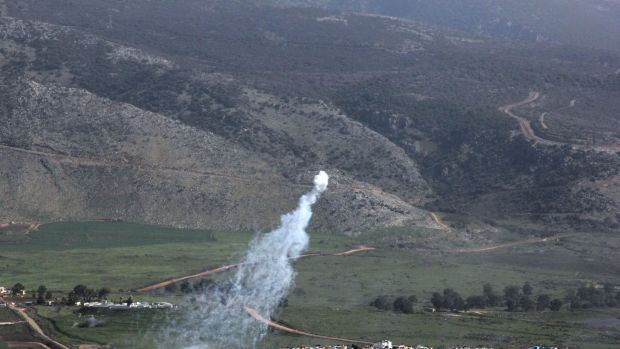 Smoke from Israeli shelling covers the Lebanese town of Al-Majidiyah (L) on the Lebanese border with Israel.