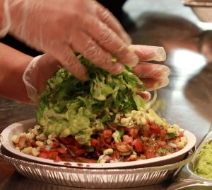 The final touches are added to a Burrito Bowl at a Chipotle restaurant.