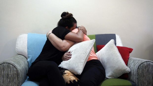 Nicolette Gomes, left, consoles her mother as they hear the news.