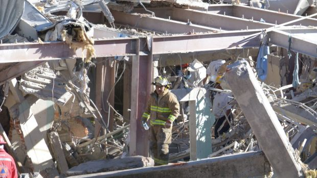 Horrific scene ... A firefighter searchers for survivors in the wreckage of the Children and Maternity Hospital in ...
