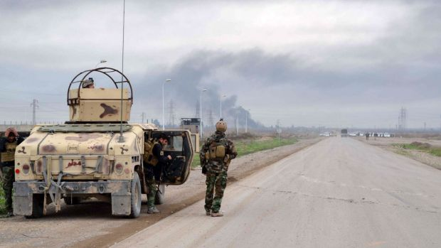 Smoke billows in the background as Kurdish peshmerga fighters take positions on the side of a road in the northern Iraqi ...