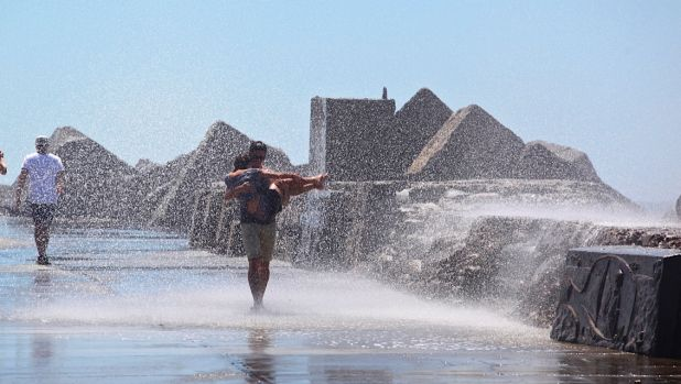 A woman who fell from Nobbys breakwall in Newcastle is carried from the scene.