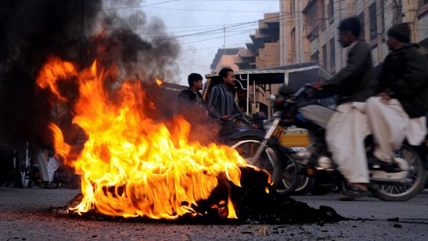 Public outrage: Tyres burn during a protest in Karachi.