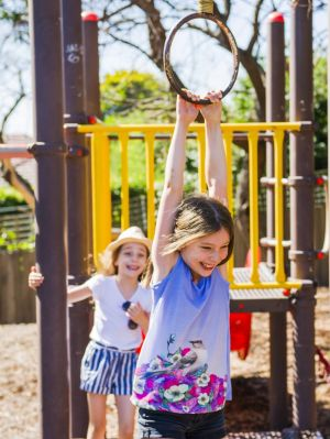 Sisters Olivia and Sophia Baker can keep playing in Narrabundah playground after the ACT government decided to repair it.
