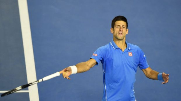 Serbia's Novak Djokovic throws his racquet into the crowd as he celebrates after his victory.