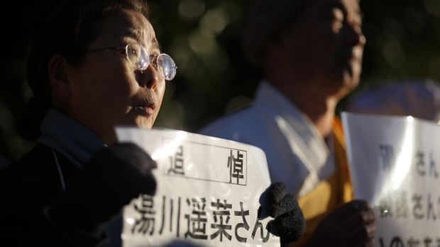 """A woman, holding a sign stating: """"In memory of Mr Haruna Yukawa,"""" takes part in a vigil outside the Japanese prime ..."""