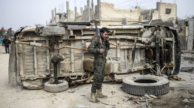 A Kurdish fighter talks on the phone in the centre of Kobane.