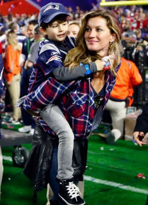 Gisele Bundchen, wife of  Tom Brady of the New England Patriots, walks on the field with their son, Benjamin.