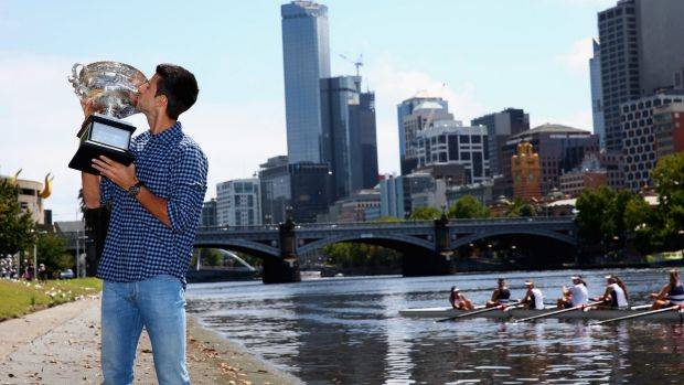 Novak Djokovic with his trophy on the banks of the Yarra on Monday.