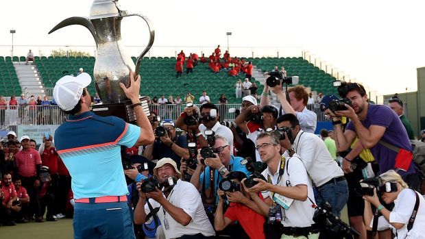 Heavy lifting: Rory McIlroy of Northern Ireland with the winners trophy after the final round of the Omega Dubai Desert ...