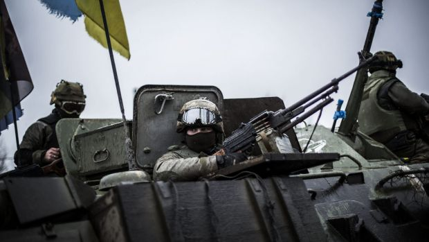 Ukrainian soldiers are seen in an armoured vehicle topped with a Ukrainian flag near the city of Artemivsk, in the ...