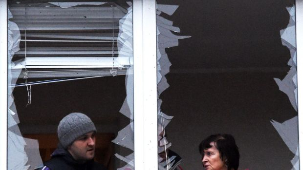 People repair windows in a flat after it was damaged by shelling in the eastern Ukrainian city of Donetsk.