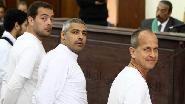 Mixed feelings about leaving his colleagues behind: Peter Greste (right) and co-defendants, Al-Jazeera English producer ...