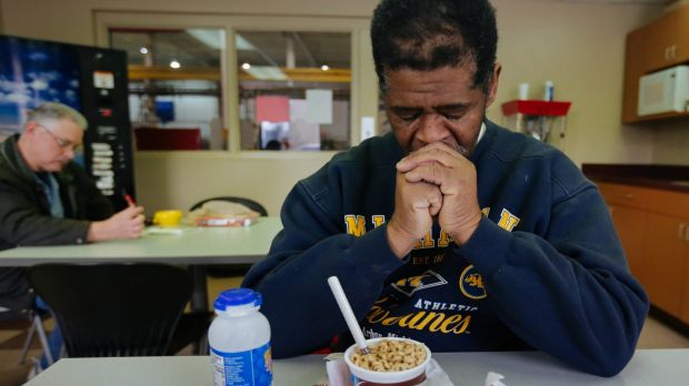 James Robertson prays before eating in the break room before his shift at Schain Mold & Engineering in Rochester Hills, ...