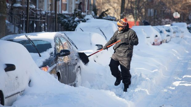 Chicago resident Marcus Neris digs his car out of the snow.