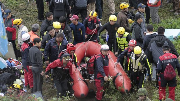 Emergency personnel carry an inflatable dinghy to try to extract passengers from the plane after it crashed in a river ...