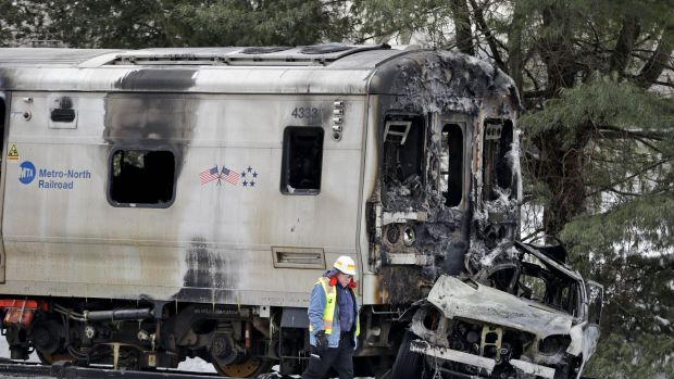 Men wearing Federal Railroad Administration vest looks over the wreckage of a Metro-North Railroad train and a Jeep SUV ...