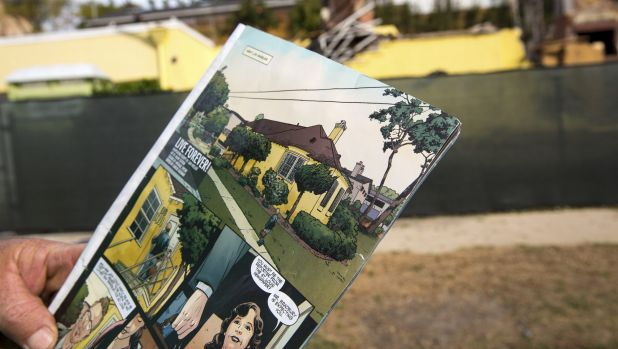 A demolition worker holds a comic book featuring Ray Bradbury's home in the background, now mostly torn down.