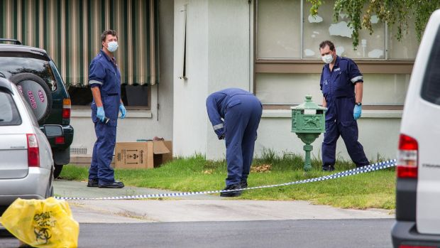Police at the home where a woman's body was discovered.