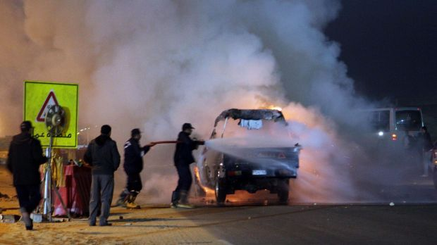 Firefighters try to extinguish a fire on a truck after a riot broke out outside of a major soccer match between Egyptian ...