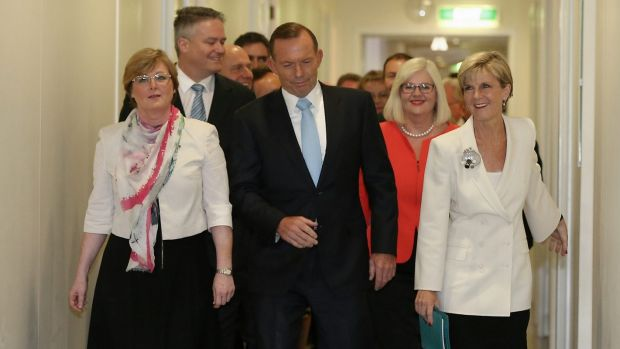 Tony Abbott is flanked by his ministers and loyal MPs as he arrives for the party room meeting on Monday.