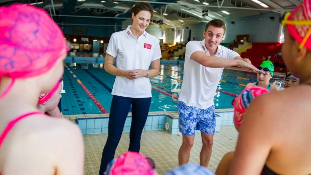 Matt Cowdrey joins Cate Campbell in giving young children swimming tips in Canberra last year.