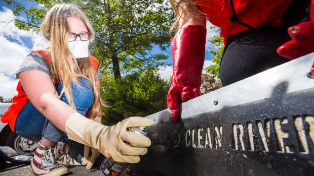Year 11 student Hanna Gardiner, 16, stencils a message on a storm water drain to let the community know it runs into the ...
