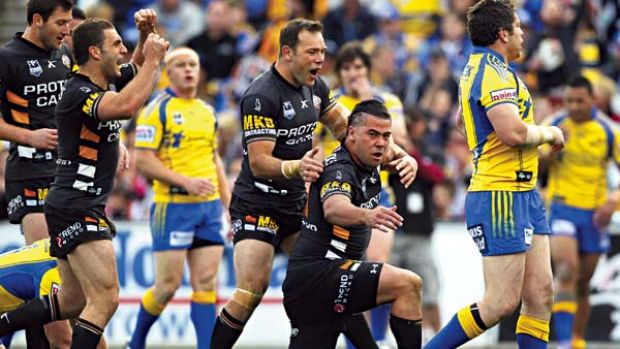 Very handy, Andy ... Tigers players rush in to congratulate Andrew Fifita onhis 63rd-minute try.