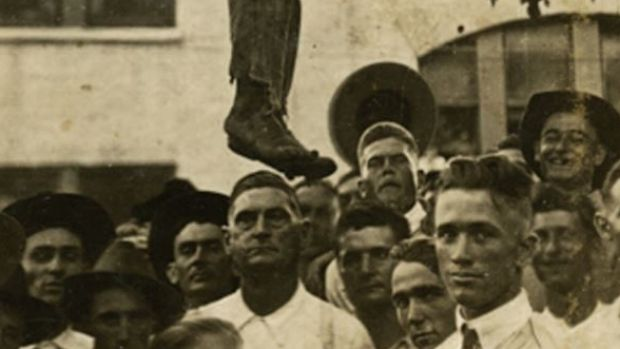 A white crowd stands below the hanging body of a black man in Texas in 1920.
