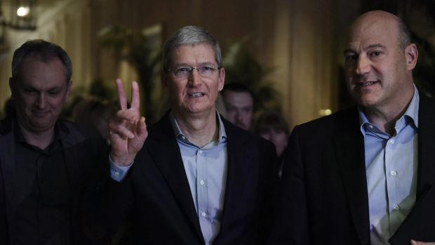 Apple CEO Tim Cook, centre, arrives to speak with Gary Cohn, president and COO of Goldman Sachs, right, at the event ...