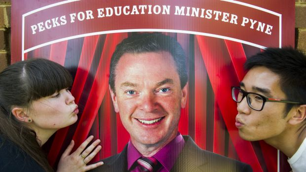 ANU politics students Caity Cameron and Nelson Tang prepare to kiss a picture of Chistopher Pyne at the ANU.