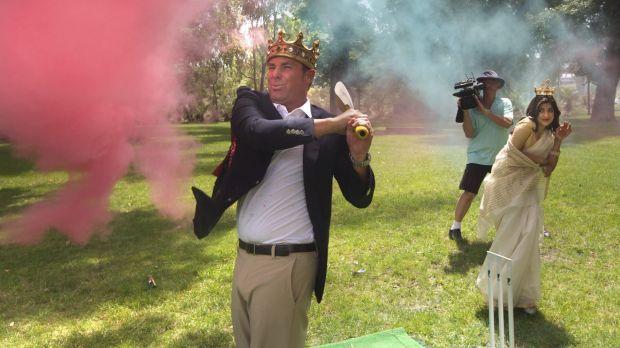 Warnie tries out his crown while hitting some cricket balls filled with coloured powder.