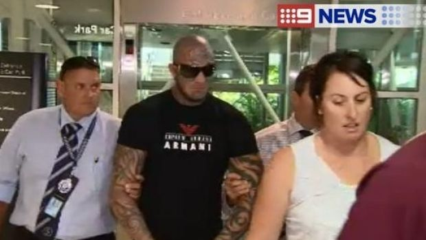 Alleged bikie Brett Pechey is taken into custody at Brisbane Airport.
