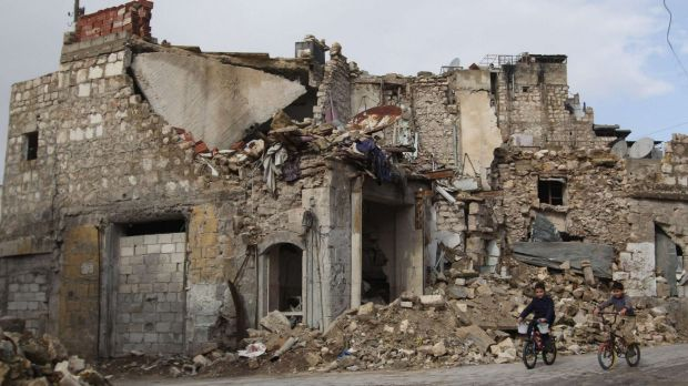 Boys ride bicycles past a damaged building in the Bab al-Nasr neighbourhood of Aleppo in Syria.