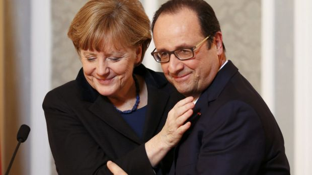 Germany's Chancellor Angela Merkel embraces France's President Francois Hollande during a meeting with the media after ...