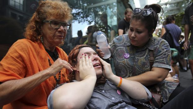 University student Anna Amelia (centre) who was pepper sprayed by police when protesters stormed the Sydney Masonic ...