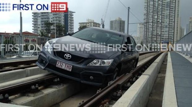 A police car racing to the scene of a fatality on the Gold Coast became wedged in tram tracks.