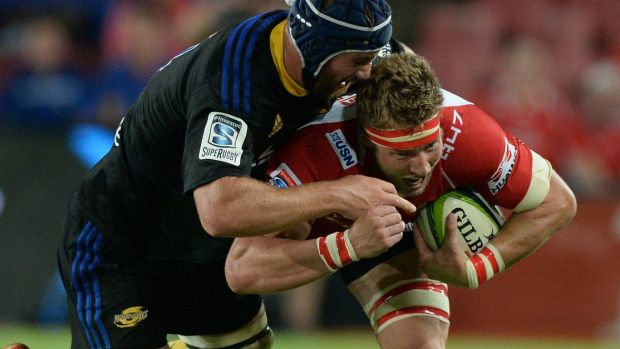 Committed defence: Mark Abbott of the Hurricanes latches on to Robert Kruger of the Lions.
