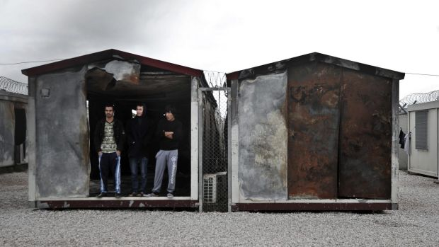 Immigrants at the entrance of a container in the detention centre.