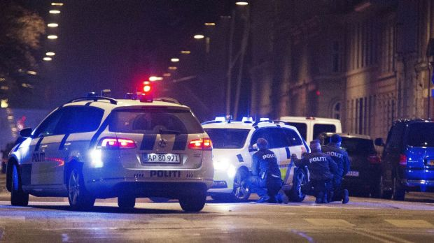 Police take cover in a street in central Copenhagen early on Sunday morning following a fatal shooting at a synagogue in ...