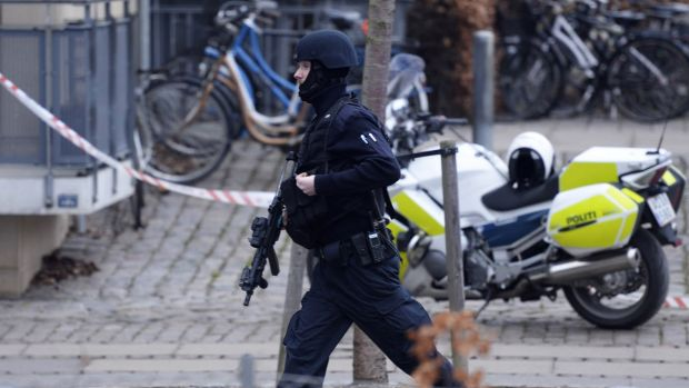 An armed security officer runs down a street near a cafe after shots were fired at a debate on free speech on Saturday.