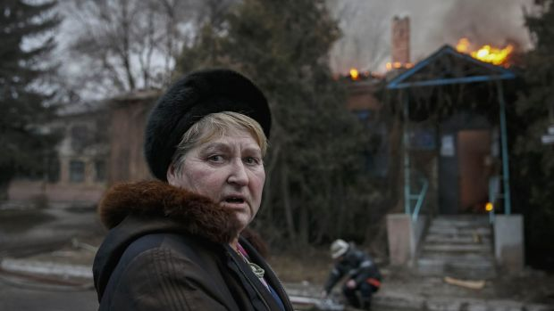 A woman in front of a burning building after shelling in Artemivsk, eastern Ukraine on Saturday, hours before the ...